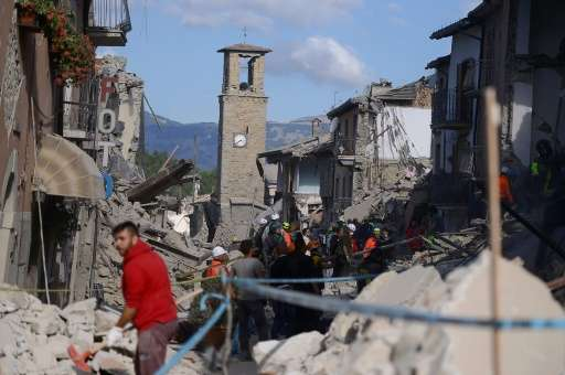 Rescuers and firemen search the rubble of buildings in Amatrice, central Italy on August 24, 2016 following the earthquake that