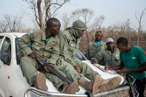 Researcher Martial Kiki (right) fills in data sheets with rangers during a lion population estimate at Nigeria's Yankari Game Re