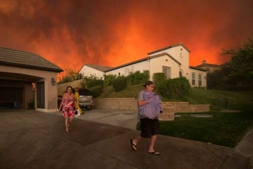 """Residents flee their home as flames from the blaze dubbed """"Sand Fire"""" rages, on July 23 2016 near Santa Clarita, Calif"""