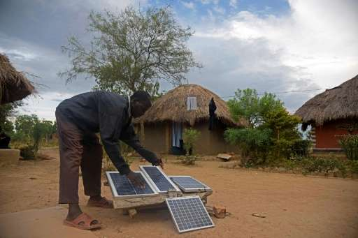 Robert Otala checks on solar panels that he uses for his home in Soroti District about 300 kilometres northeast of the capital K