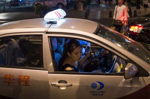 Taxis, like this one a woman is getting into on a street in the southern Chinese city of Shenzhen on April 24, 2015, are threate
