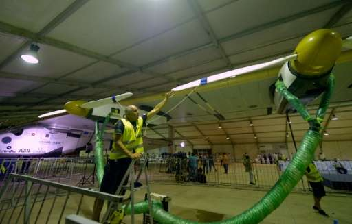 Technicians prepare the solar-powered Solar Impulse 2 aircraft at the Cairo International Airport on July 23, 2016