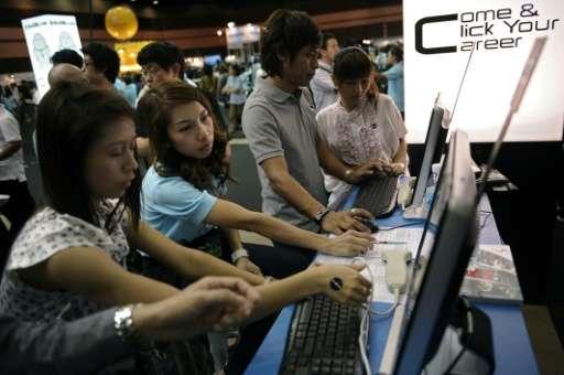 Thai workers look at job advertisements in Bangkok