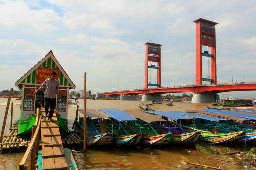 This picture taken in Palembang on March 7, 2016 shows the city's icon the Ampera bridge on the Musi river where tourists and lo