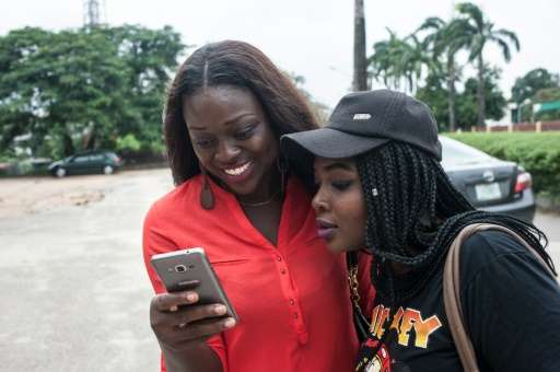 Two friends use the Pokemon Go application on their mobile phones on the campus grounds of the University of Lagos on July 14, 2