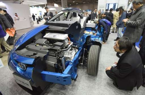 Visitors look at a cutaway model showing the fuel cells of a Toyota MIRAI car in Tokyo on December 10, 2015