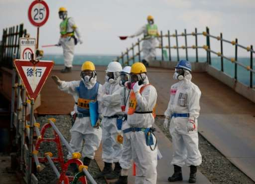 Workers, wearing protective suits and masks, are seen near the No. 3 and No.4 reactor buildings at the  Fukushima Daiichi nuclea