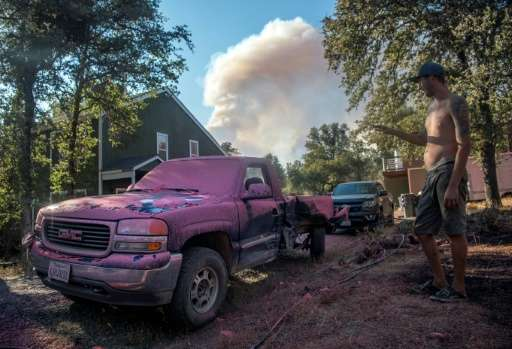 A man covers his truck in fire retardant as smoke billows outside the town of Oroville, California. About 5,000 firefighters wer