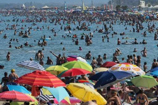 Holidaymakers enjoy the beach in Canet-en-Roussillon, France on August 4, 2017 during a heat wave
