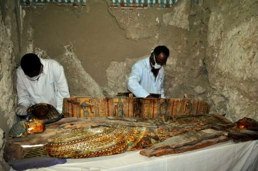 Members of an Egyptian archaeological team work on a wooden coffin discovered in a 3,500-year-old tomb in the Draa Abul Nagaa ne