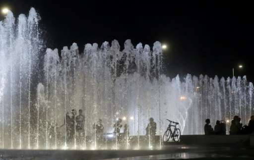 People sit next to a water fountain in the centre of Zagreb at night as southern Europe and the Balkans face a heatwave with tem