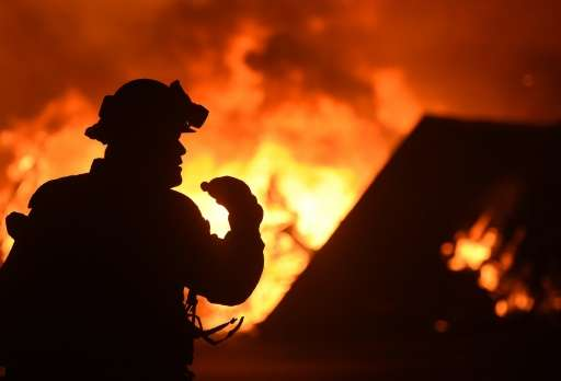 A firefighter drinks water in front of a burning house near Oroville, California on July 9, 2017. Crews are battling the season'
