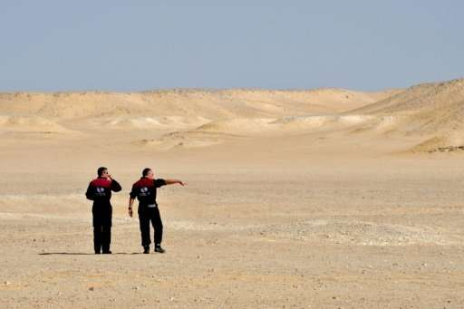 Members of the Austrian Space Forum inspect a site in Oman's Dhofar desert, near the southern Marmul outpost, on October 29, 201