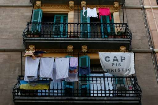 """A banner reading, """"No tourist flats"""" hangs from a balcony to protest against holiday rental apartments for tourists in"""