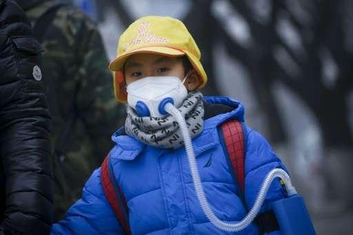 A boy wears an oxygen mask as he walks along a road in Beijing on January 5, 2017