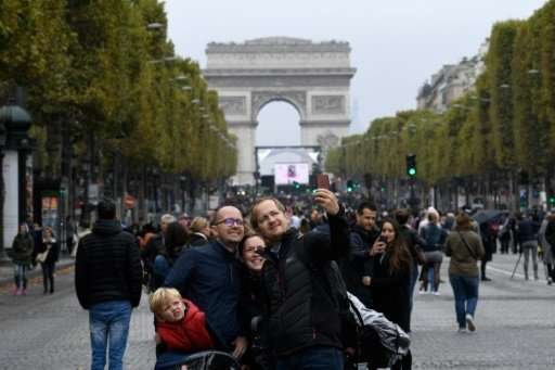 """A family posses for a selfie along the Champs-Elysees with the Arc de Triumph as a backdrop during a """"car free"""" day in"""