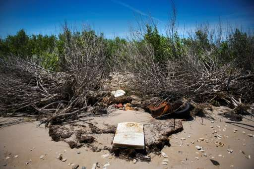 A grave stone rests on the beach where a cemetery once stood but has been washed away due to erosion in an area called Canaan in