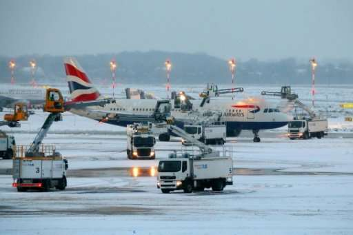 An airplane of British Airways is being de-iced as it stands on the tarmac of the airport in Duesseldorf, western Germany, on De