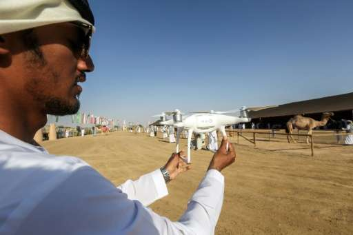 An Emirati holds up a camera-equipped drone in Al-Ain on the outskirts of Abu Dhabi, on February 8, 2017