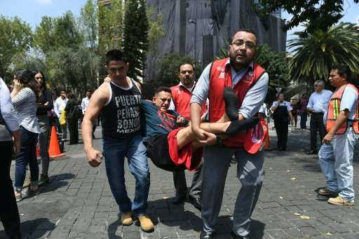 An injured man is carried away by rescuers in Mexico City