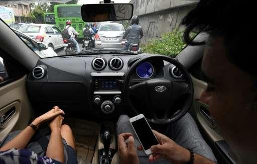 Ankur Bhatia (R), head of marketing at Mahindra Electric Mobility, checks his mobile phone while driving Mahindra's electric car