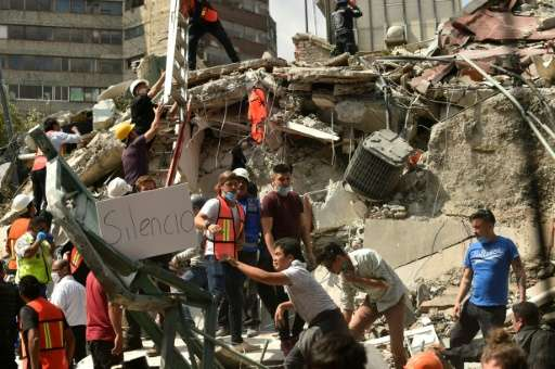 "A placard reads ""Silence"" as rescuers hurry to free possible victims out of the rubble of a collapsed building in Mexi"