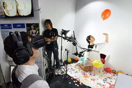 At FutureLeap's booth, a young model kneels on a fluffy carpet as she tosses balloons in the air, blows bubbles and flirts with