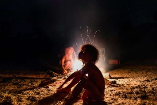 A Waiapi boy sits by a bonfire at Manilha village in Brazil's Amapa state