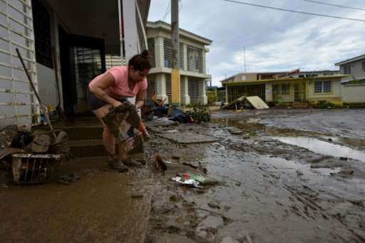 A woman removes mud from her damaged house in Toa Baja, near San Juan, Puerto Rico