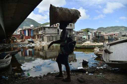 A woman walks next to the Mapou River, in Shada neighborhood, in Cap-Haitien, in the north of Haiti, where hurricane preparation