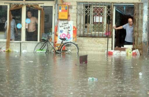 Chinese residents look at a flooded area caused by heavy rain in Beijing