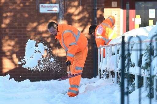 Council workers clear a path to the entrance to a retirement home near Wrexham, north Wales, on Monday