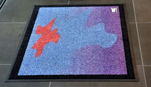 It may look like an ordinary door mat, but its creators insist the conceptual art piece could encourage alien life to visit Eart