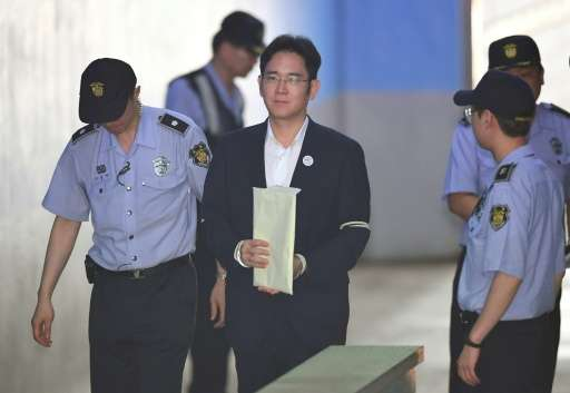 Lee Jae-Yong, the vice-chairman of Samsung Electronics, is escorted by prison guards as he arrives in court