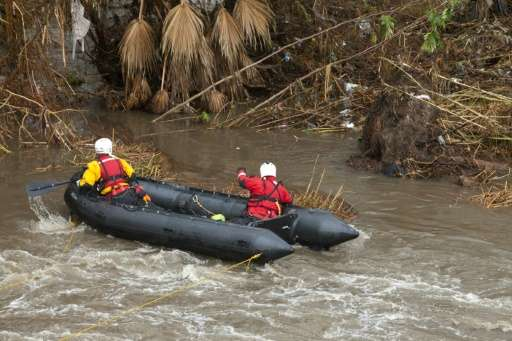 Los Angeles rescuers look for a drowning victim in the LA River as storms across the state dump rain and snow which could herald