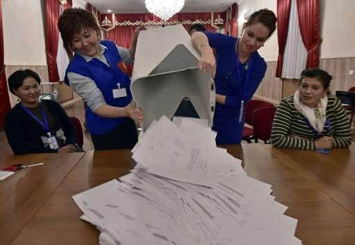 Members of a local election committee empty a ballot box. Some have said the timing of the reburial—on the eve of an October 15