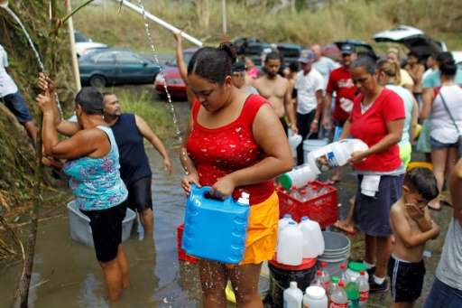 People collect water from a natural spring created by the landslides in a mountain next to a road in Corozal, west of San Juan,