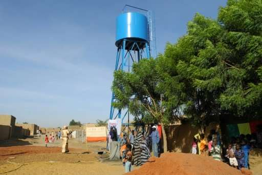 People draw water from a brand new well after its inauguration in the Tagoute area of Gao