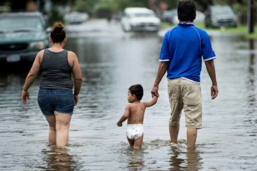 People walk through flooded streets in Galveston as heavy rains from Harvey leave a trail of destruction