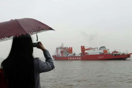Picture taken on October 30, 2014 shows a woman taking a photo with her mobile phone as Chinese research vessel and icebreaker X