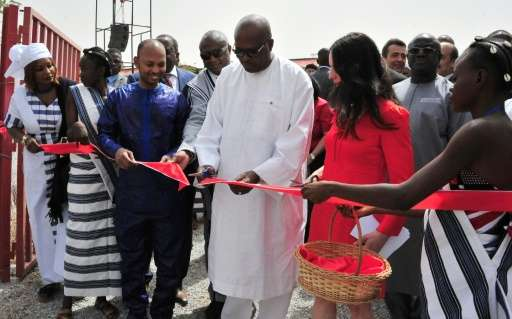 President of Burkina Faso Roch Marc Christian Kabore (C) cuts the ribbon during the inauguration of a new movie theatre which ru