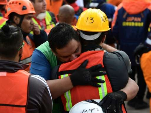 Rescue workers embrace after the seismic alert sounded in Mexico City