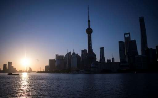 The sun rises over the Huangpu River, seen against the skyline of the Lujiazui Financial District in Pudong in Shanghai on May 1