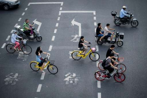 Two men (centre) riding bicycles from a sharing company in Shanghai