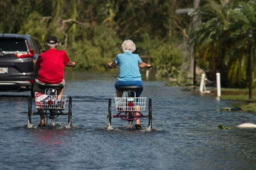 Two retirees ride tricycles through a flooded street in Naples, Florida