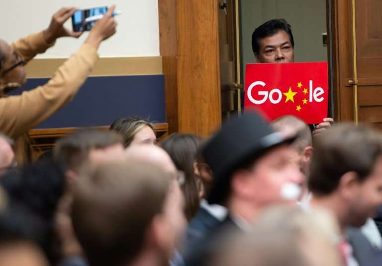 A demonstrator holds a sign in protest as Google CEO Sundar Pichai testifies during a House Judiciary Committee hearing that exa