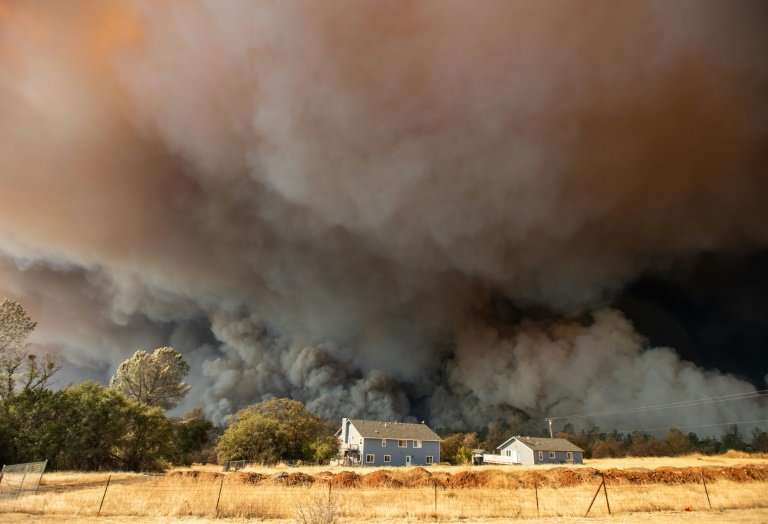 A home is overshadowed by towering smoke plumes in Paradise, which was wiped off the map by the Camp Fire