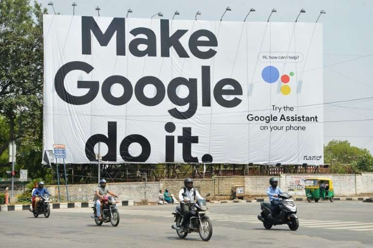 Indian commuters in Bangalore ride past an advertisement poster for Google, which is overhauling its Gmail service