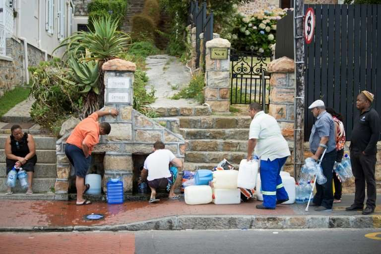 People collect drinking water from pipes fed by an underground spring