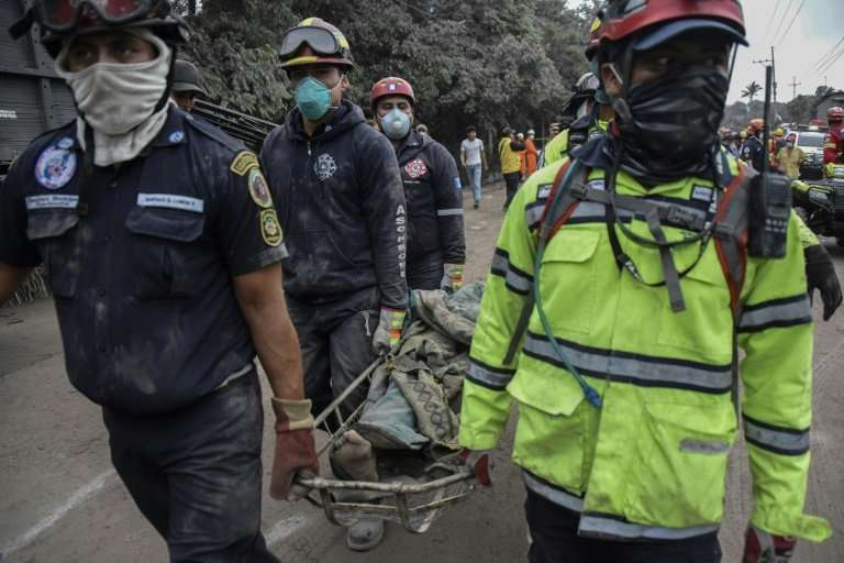 Police officers carry a victim in the ash-covered village of San Miguel Los Lotes, in Escuintla Department